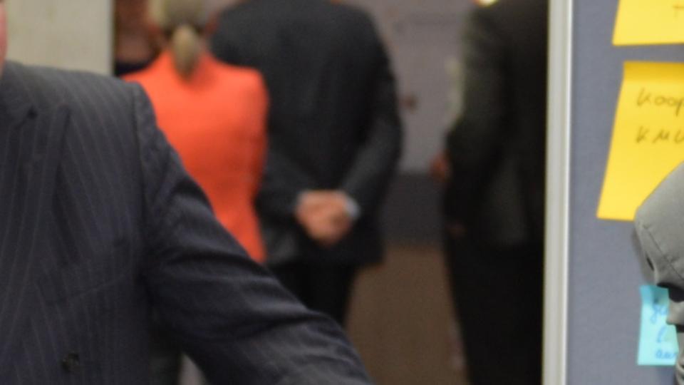Minister Lienenkämper in steht in der Diskussionsrunde neben einer Pinnwand.