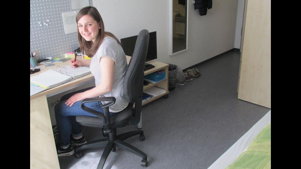 Zimmer in der LFSch_Mädchen sitzt am Schreibtisch und lächelt in die Kamera