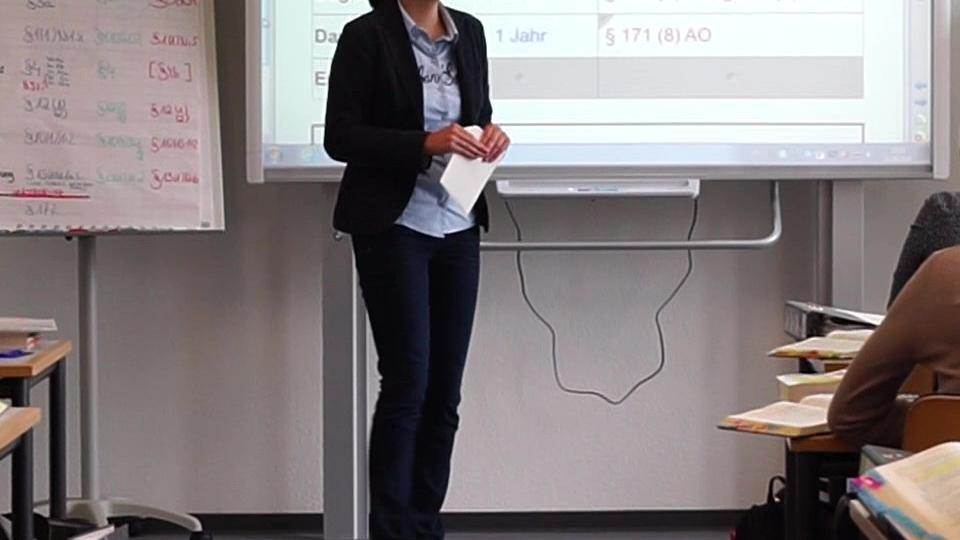 eine Dozentin steht vor ihrer Klasse